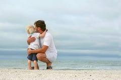 Vater und junger Sohn, die heraus über Ozean schauen stockbild