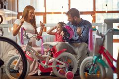 Vater und kaufendes neues Fahrrad und Sturzhelme der Mutter für wenig Mädchen stockfoto
