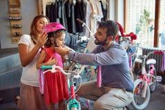 Vater und kaufendes neues Fahrrad und Sturzhelme der Mutter für wenig Mädchen im Fahrradgeschäft stockbilder
