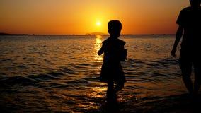 Vater und Kind, die auf dem Strand zur Sonnenuntergangzeit spielen Konzept der Familie stockfotos