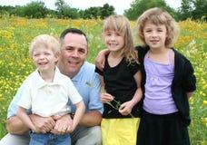 Vater und Kinder auf dem Blumen-Gebiet Stockfoto