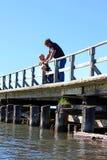 Vater und Kinder auf Dock über See Stockfotos