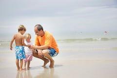 Vater und Kinder auf Strand Lizenzfreie Stockbilder