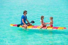 Vater und Kinder auf Surfbrett während des Sommers Stockfotografie