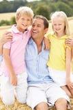 Vater und Kinder, die auf Stroh-Ballen in Harv sitzen Lizenzfreie Stockbilder