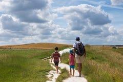 Vater und Kinder, die in Landschaft gehen stockfotos