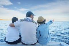 Vater und Kinder, die Meerblick auf dem Schiff genießen Stockfotografie
