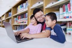 Vater und Kinder, die online zusammen in der Bibliothek lernen Lizenzfreie Stockfotos