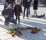 Vater und Kinder, die Respekt zum ermordeten Haupt-minist zeigen Lizenzfreie Stockfotografie