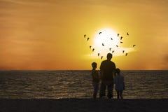 Vater und Kinder, die schönen Sonnenuntergang genießen Lizenzfreie Stockfotografie