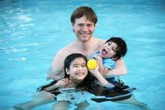 Vater und Kinder im Pool Stockfotografie
