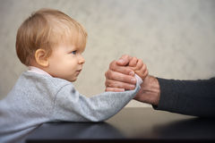 Vater- und Kinderarmdrückenwettbewerb Stockbilder