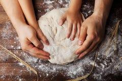 Vater- und Kinderhände bereitet den Teig mit Mehl, Nudelholz und den Weizenähren auf rustikalem Holztisch von oben zu stockbild
