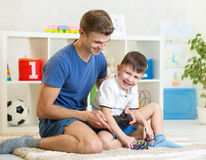 Vater- und Kinderjunge spielen mit RC-Hubschrauberspielzeug Stockfotografie
