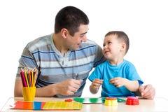Vater und Kinderspiel mit Lehm zusammen Stockbild