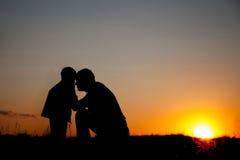 Vater und Kindsonnenuntergang, Schattenbild gegen den Abendhimmel lizenzfreie stockfotografie