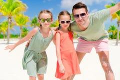 Vater und kleine Mädchen, die Spaß auf weißem Strand in der Palmenwaldung haben stockfotografie