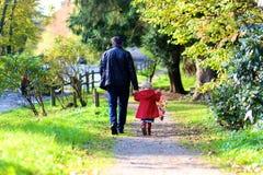 Vater und kleine Tochter, die in den Park gehen Stockfotos
