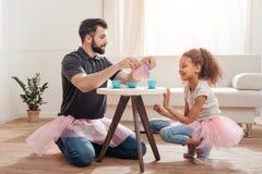 Vater und kleine Tochter, die Teeparty zu Hause haben Lizenzfreie Stockfotografie