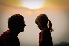 Vater und kleine Tochter am Sonnenunterganghimmel Lizenzfreies Stockbild