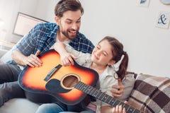 Vater und kleine Tochter zu Hause, die den Mann umarmt die Tochter spielt die Gitarre froh sitzt stockfoto