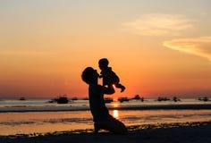 Vater und kleine Tochterschattenbilder auf Sonnenuntergang setzen auf den Strand Stockfotografie