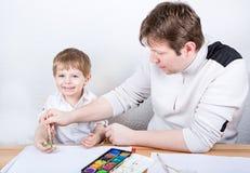 Vater und kleiner Junge von zwei Jahren Spaßmalerei habend Lizenzfreies Stockfoto