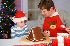 Vater und kleiner Sohn, die ein Lebkuchenplätzchenhaus vorbereiten Lizenzfreie Stockfotos