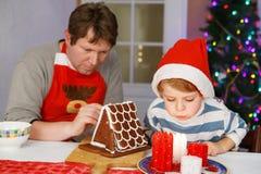 Vater und kleiner Sohn, die ein Lebkuchenplätzchenhaus vorbereiten Stockbilder