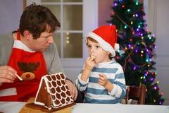 Vater und kleiner Sohn, die ein Lebkuchenplätzchenhaus vorbereiten Stockfotos