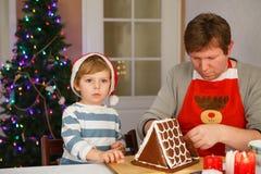 Vater und kleiner Sohn, die ein Lebkuchenplätzchenhaus vorbereiten Stockbild