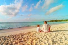 Vater und kleiner Sohn, die Meer auf Strand betrachten Lizenzfreie Stockfotografie