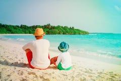Vater und kleiner Sohn, die Meer auf Strand betrachten Lizenzfreies Stockfoto