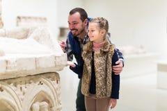 Vater und kleines Mädchen, die alte Flachreliefs erforschen Stockfotografie