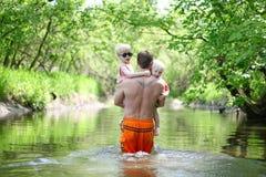 Vater und Kleinkinder, die in Fluss im Wald gehen stockbilder