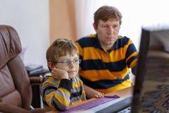 Vater- und Kleinkindjunge, der an Schulhausarbeit lernt und macht Stockfotografie
