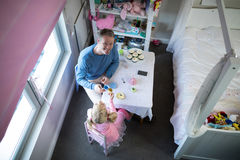 Vater und Mädchen, die ihre Teeschalen beim Spielen mit Spielzeugküchensatz rösten Stockbilder