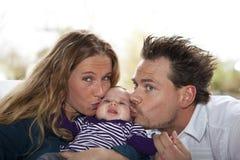 Vater und Mutter, die ihr Baby küssen Stockbild