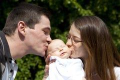 Vater und Mutter, die ihre schlafende Tochter küssen Stockbilder
