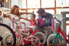 Vater und Mutter, die neues Fahrrad und Sturzhelme f?r wenig M?dchen kaufen stockbild