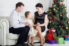 Vater und Mutter sprechen mit Tochter auf Sofa nahe Weihnachtsbaum Stockbild