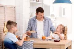 Vater und nette kleine Kinder, die frühstücken Stockbilder