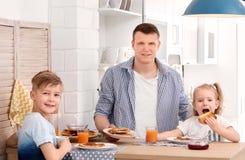 Vater und nette kleine Kinder, die frühstücken Lizenzfreies Stockbild
