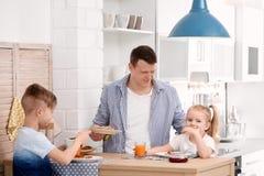Vater und nette kleine Kinder, die frühstücken Lizenzfreie Stockfotografie