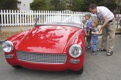 Vater und Söhne behandelten das kleine rote Weinlesekabriolett Stockfoto