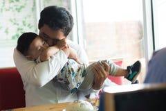 Vater und sein Sohn, die zuhause Kuchen am Caf? sitzen und essen lizenzfreie stockfotos