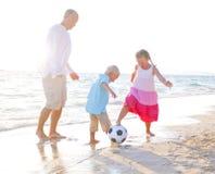 Vater und seine Kinder, die zusammen Fußball spielen Stockbilder