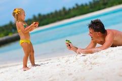 Vater und seine Tochter auf exotischem Strand Lizenzfreie Stockfotos