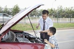 Vater und Sohn überprüfen das Öl auf ihrem Auto Stockbild