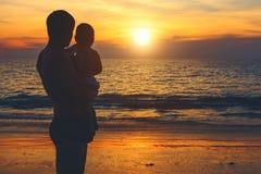 Vater und Sohn auf dem Ufer des azurblauen Meeres aufpassend für Sonnenuntergang Lebensstil, Ferien, Glück, Freudenkonzept Freize lizenzfreies stockfoto